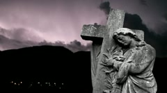 Graveyard statue set against storm clouds with lightning strikes Stock Footage