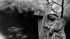 Graveyard statue set against timelapse bare tree - stock footage