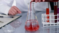 Scientist pouring red liquid into erlenmeyer flask with transparent fluid HD Stock Footage