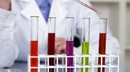 Using pipette to add red substance to test tubes with chemicals HD Stock Footage