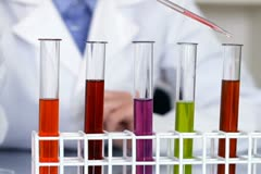 Using pipette to add red substance to test tubes with chemicals NTSC Stock Footage