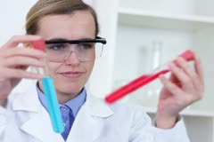 Female scientist comparing test tubes with red and blue fluid substance NTSC - stock footage