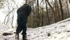 Man walking up snow covered path Stock Footage