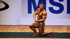 Bodybuilder poses on stage at Open Cup of bodybuilding of Moscow - stock footage