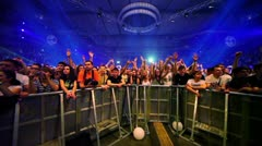 Many people stand behind fencing at Armin Only show in concert hall Stock Footage