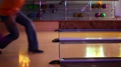 Two men throw bowling ball one by one on parallel lanes in club Stock Footage