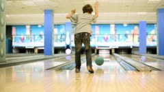 Little boy throws bowling ball to beat skittles, view from behind Stock Footage
