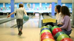 Parents sit and watch little boy throws bowling ball to beat skittles Stock Footage