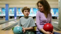 Mom and son hold bowling balls in hands and talk in bright club Stock Footage