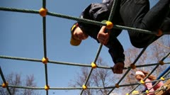 Kids climb on rope lattice at playground, closeup view from below Stock Footage