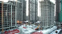 Workers and building materials at construction site in foreground of cityscape Stock Footage
