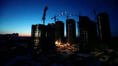 Workers at construction site in foreground of dormitory area cityscape Stock Footage