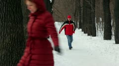 Man catches up with woman among trees at park lane Stock Footage