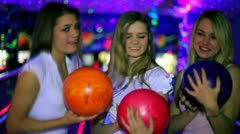Three girls stand with bowling balls and then throw it to beat skittles Stock Footage