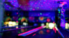 Young girl throws bowling ball to beat skittles, in club unfocused Stock Footage