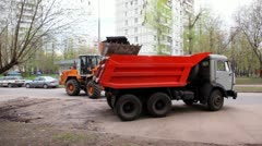 Excavator loads truck at city street at summer day Stock Footage