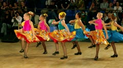 Several children in shoes with taps and colorful costumes tap dance Stock Footage