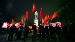 Several communists stand with flag in front of monument at approved meeting - stock footage