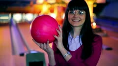 Girl hold bowling ball and smile, and then throws it to beat skittles Stock Footage