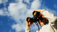 Inquisitive boy looks through binoculars against sky with clouds Stock Footage