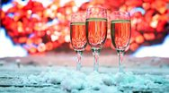 Stock Video Footage of three glasses champagne or white wine stand sprinkled snow