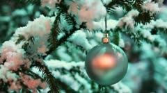 Glass ball silver color hangs on snow covered fir in winter forest Stock Footage