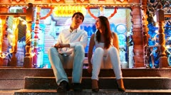 Couple sits and talks at doorway Stock Footage