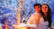 Stock Video Footage of couple sits on lighted balcony in snowy birch forest at night