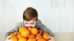Boy with a lot of apples and oranges Stock Footage