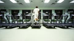 man quickly runs on treadmill in large empty gym - stock footage