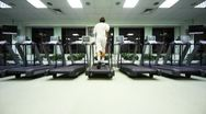 Stock Video Footage of man quickly runs on treadmill in large empty gym
