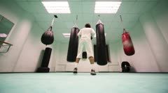 Man in gloves jumps and punches on two large heavy, then light punching bags at Stock Footage