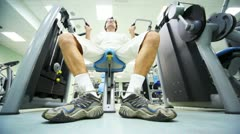 Man does exercise muscles of shoulders while sitting on exerciser and lifts Stock Footage
