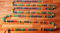 Many colored dominoes built zigzag on parquet Stock Footage