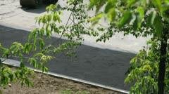 Worker stacks asphalt by steamroller AMMANN on road Stock Footage