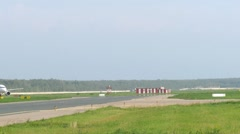 Runway is shown, green grass nearby lies, plane goes on runway Stock Footage