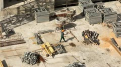 Worker goes on building site among building materials Stock Footage