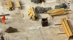Worker runs on building site among materials Stock Footage