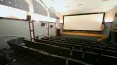 Panorama of small almost empty light cinema hall Stock Footage