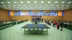 Gym with tables for table tennis and trainer with children standing in row Stock Footage