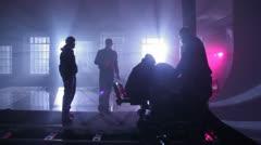 Film crew adjusts equipment on rail cart in dark room Stock Footage