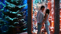 Couple stands inside lighted gazebo in winter woods Stock Footage