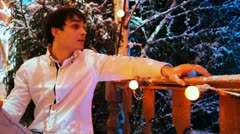 Man sits on front porch decorated with lighted lamps at night Stock Footage