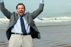 Excited businessman screaming and raising hands to the sky by the sea Stock Footage