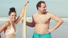 Happy young couple with surfing board standing by the sea HD Stock Footage