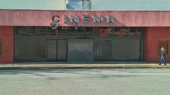 blonde woman walking by abandoned cinema buillding - stock footage