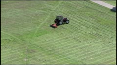 A little red tractor mower mows the grass Stock Footage