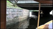 The riverboat passes under the bridge - a long shot Stock Footage