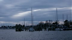 Dramatic beam of light breaks over harbor time lapse with sail boats Stock Footage