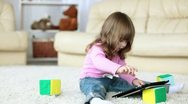 Stock Video Footage of Baby girl with tablet PC  siting on the floor